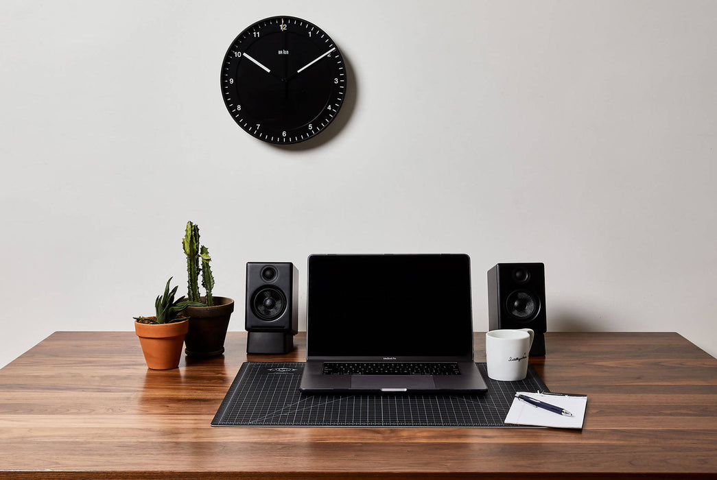 Black Analog Clock - Front View Pictured Above Desk