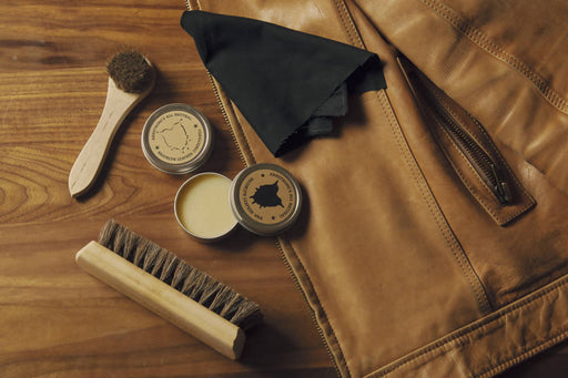 Leather care kit - aerial view of dauber, brush, cream, and cloth next to brown leather jacket