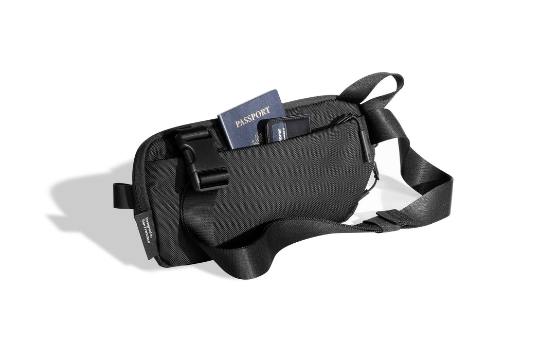Black Sling Bag Standing Up - Unzipped Rear Compartment with Passport and Wallet Pictured