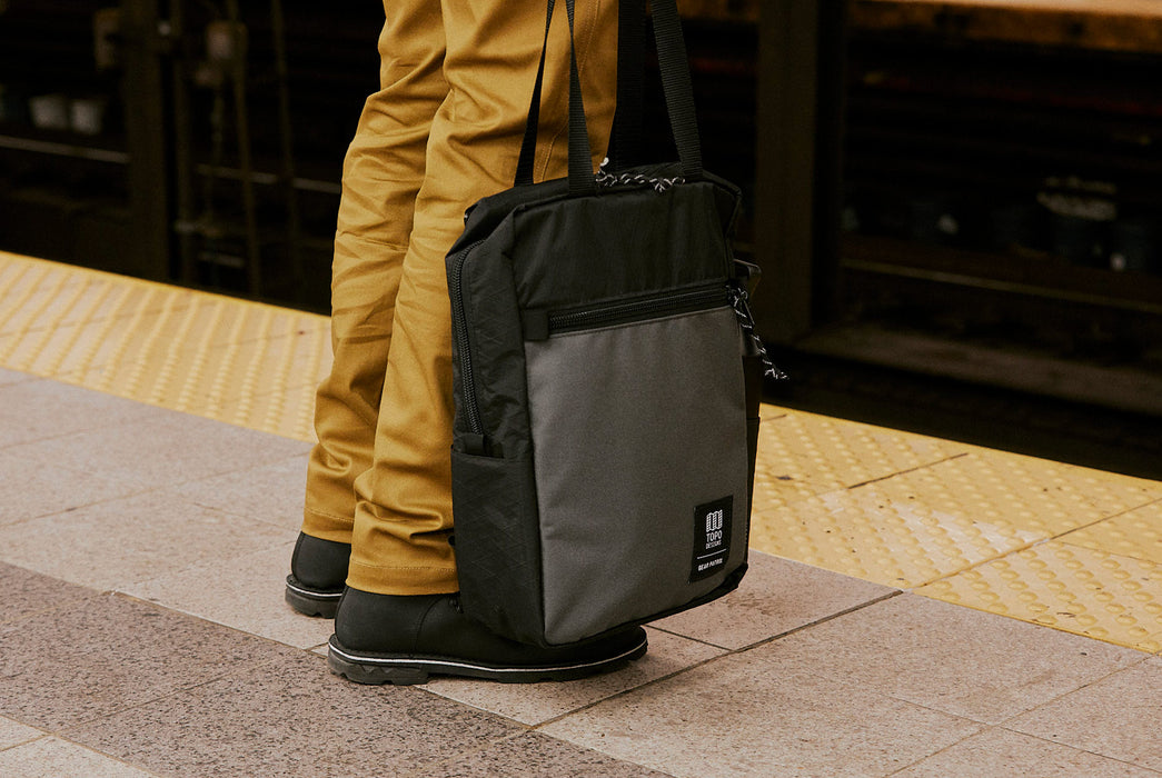 Black/Grey - Topo Designs x Gear Patrol Backpack Tote - Being held by tote straps on subway platform