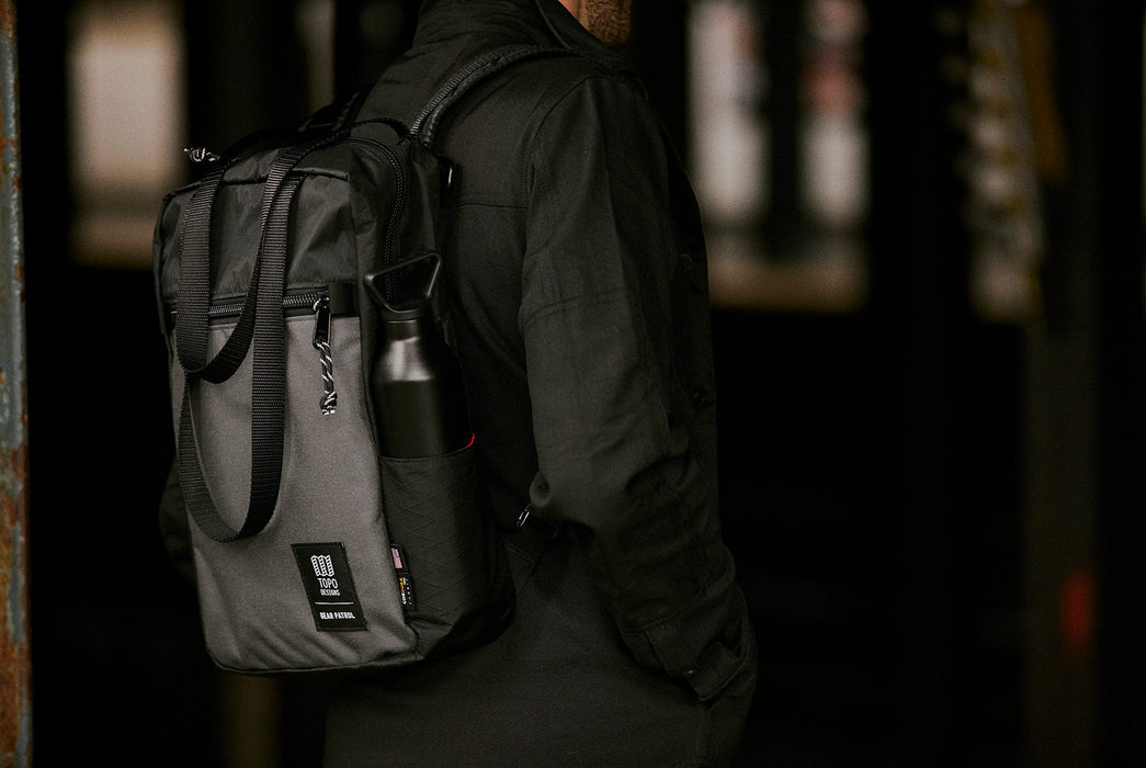 Black/Grey - Topo Designs x Gear Patrol Backpack Tote - On models back with water bottle in holder