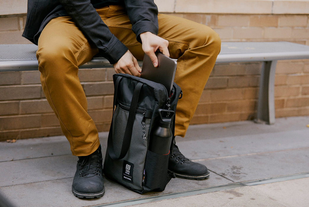 Black/Grey - Topo Designs x Gear Patrol Backpack Tote - Model putting laptop in bag while sitting on bench