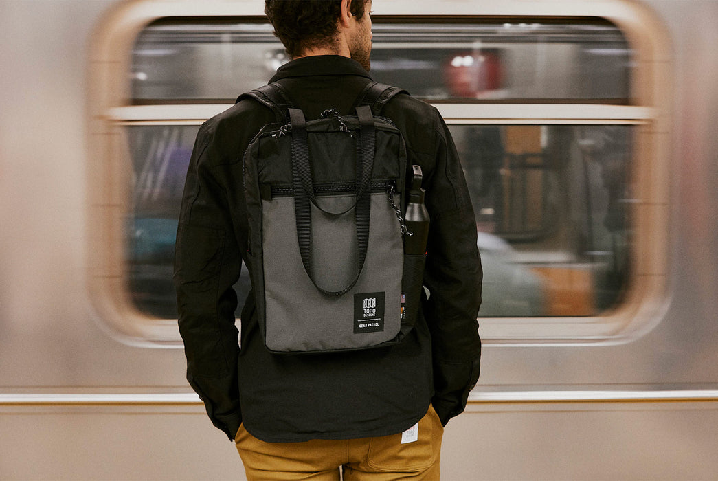 Black/Grey - Topo Designs x Gear Patrol Backpack Tote - On models back with subway train going by