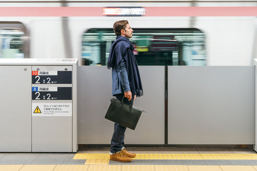 Lotuff Triumph Briefcase Bag - Black - Image of man standing in front of a subway, holding bag by top handles