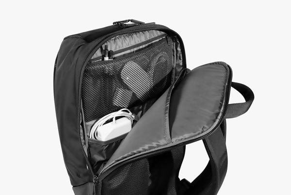 Black Duffel Pack Standing Up - Unzipped Rear View Displaying Laptop Compartment and Tech Accessories