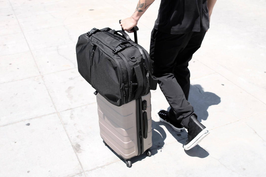 Black Travel Pack - Carried atop suitcase by model