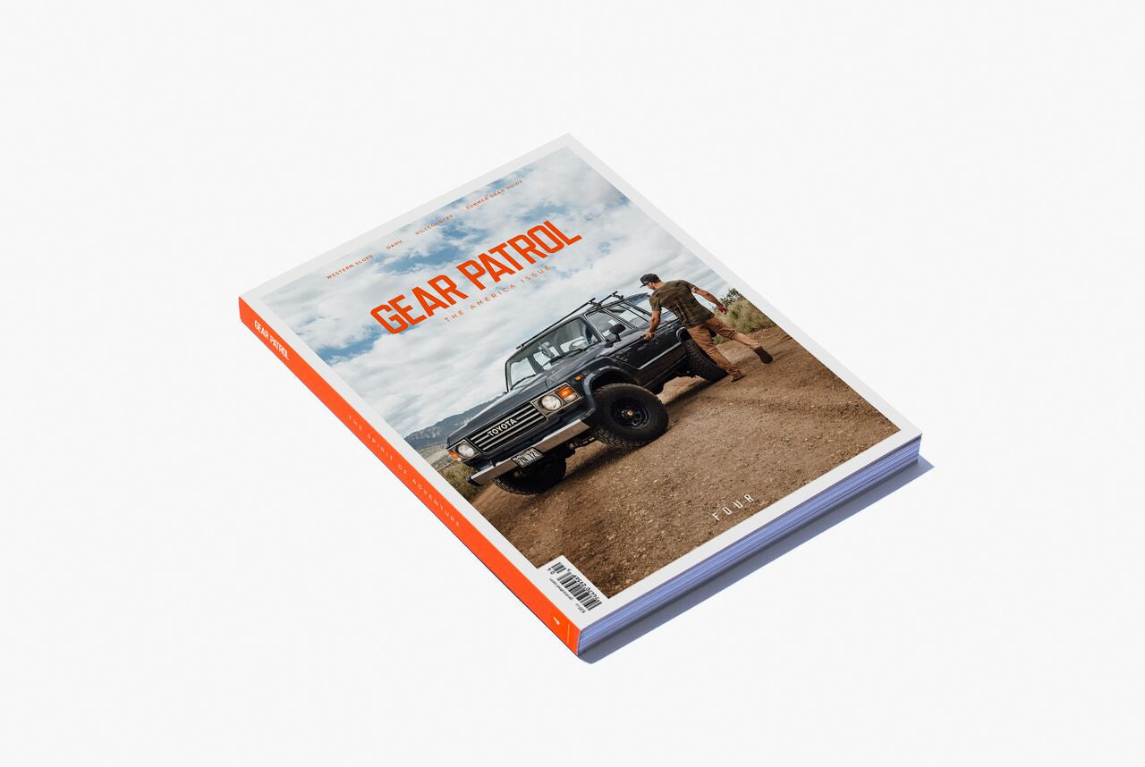 Gear Patrol Magazine: Issue Four - Cover shot of man getting into a Toyota truck on a dirt road with blue skies behind