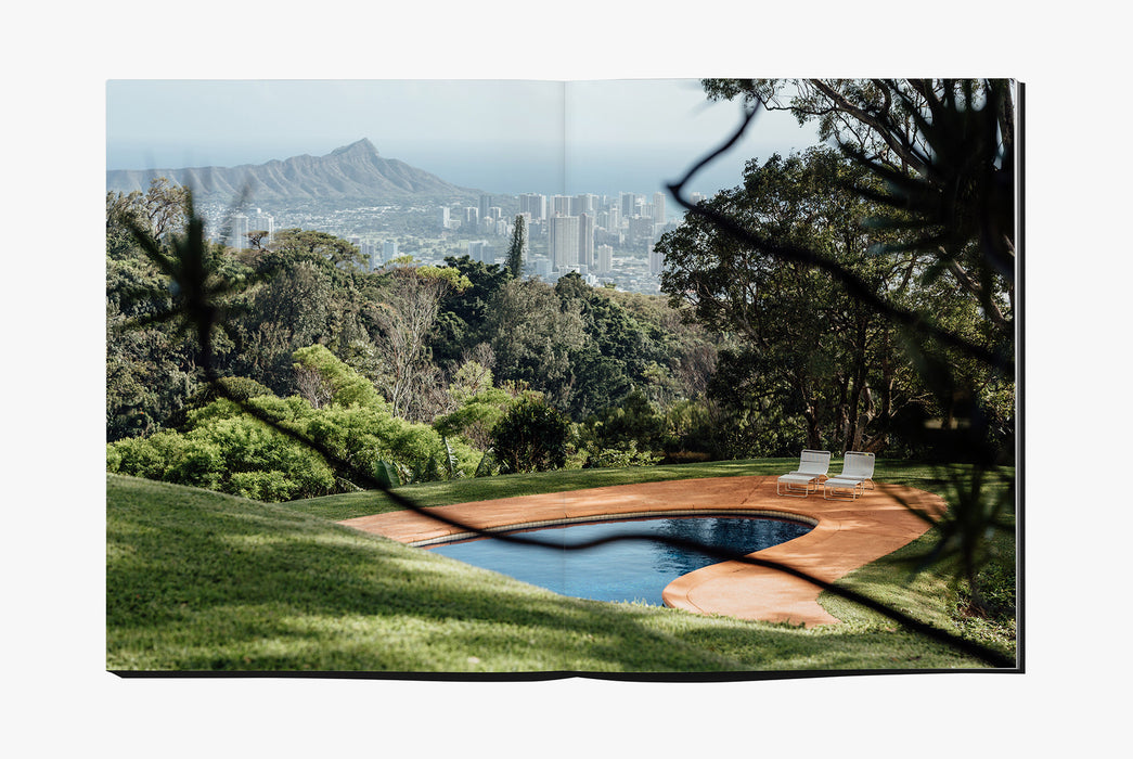 Gear Patrol Magazine: Issue Four - Open to spread showing an in-ground pool surrounded by grass, trees, and a mountain and city in the background