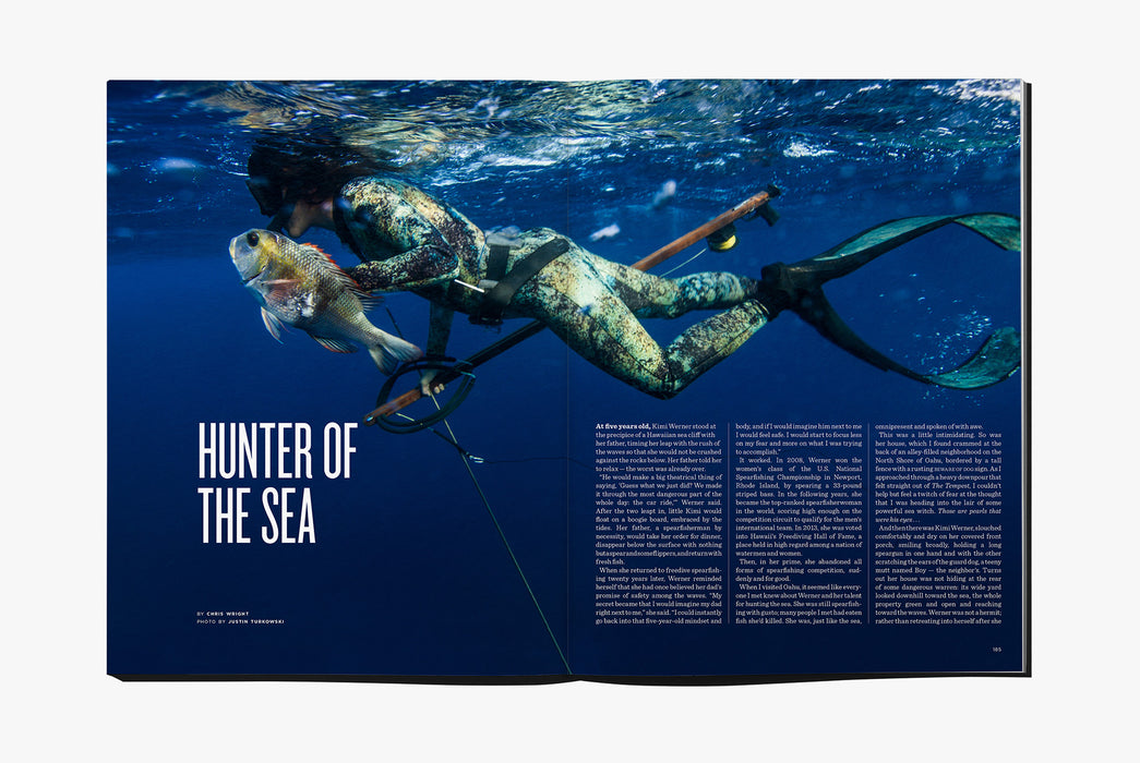 Gear Patrol Magazine: Issue Four - Open to spread showing a person in a diving suit underwater holding a spear and a fish