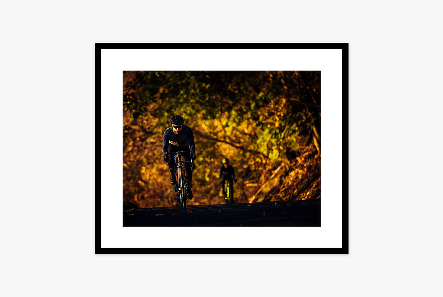 Framed photo of two bicyclists riding at night