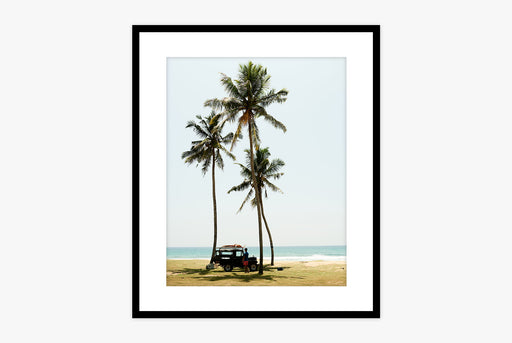 Framed photo of a truck in front of three palm trees with the beach in the background