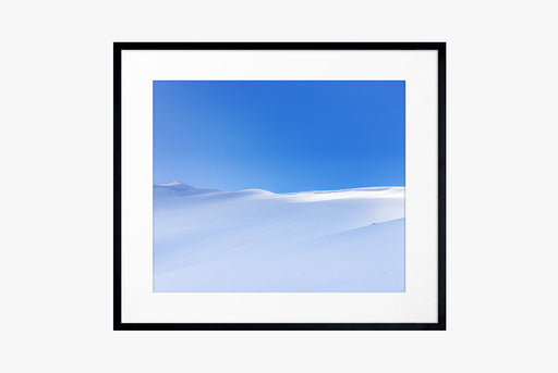 The Selkirks Print - framed photo of wide, snowy hills with a blue sky behind