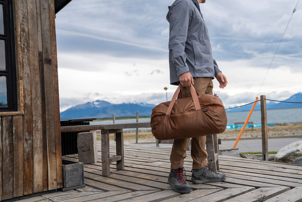Matador Transit30 2.0 Duffel Bag - Coyote - Man holding duffel bag on a boat deck