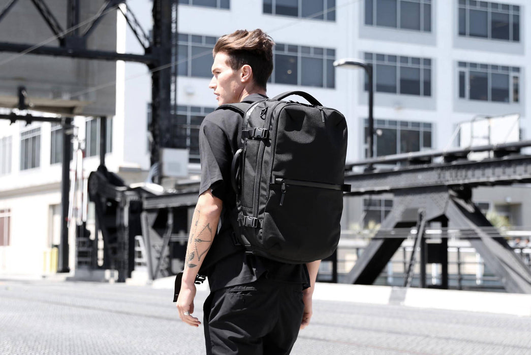Black Travel Pack worn on model's back - rear view