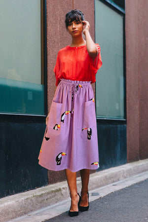 Linen lilac skirt with a draw string waist. Patch pockets.  The skirt is printed with a toucan bird print.  The skirt is midi length, coming below the knees.