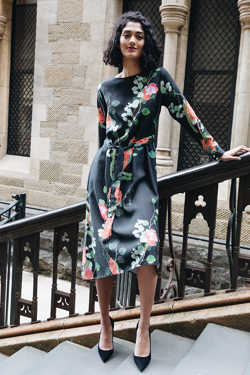 DEVOI SIBYLLE DRESS, NATIVE BLOOM PRINTED DRESS, BLACK DRESS, LONG SLEEVED SHIFT DRESS WITH A TIE BELT AND SIDE POCKETS.  THE DRESS HAS A BOAT NECK AND THE SLEEVES HAVE BUTTONED CUFFS.  DRESS IS UNLINED