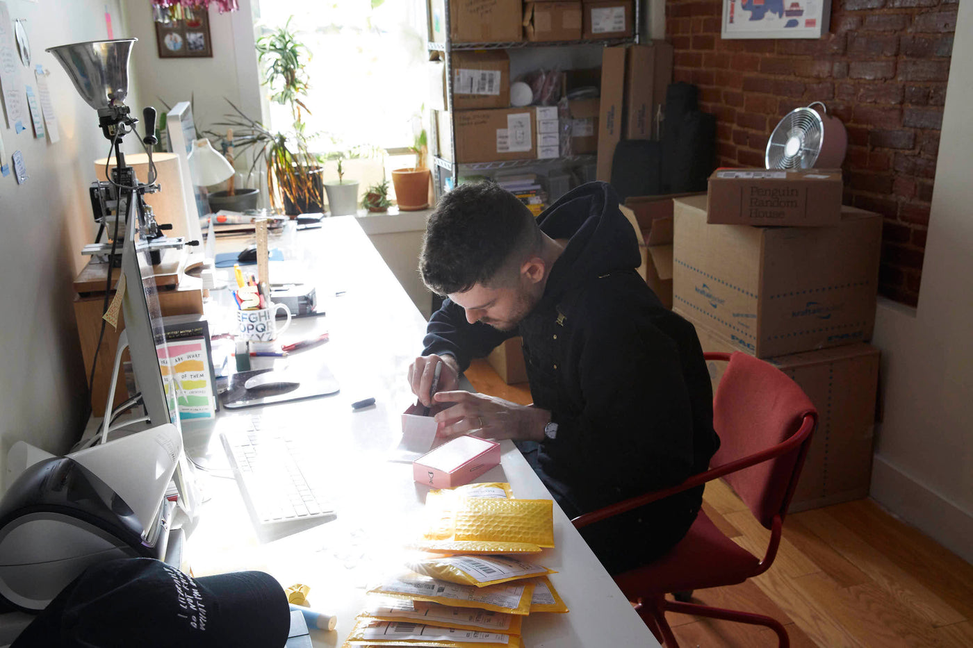 Photo of Adam hunched over work at a cluttered desk in his studio. Packages of merchandise sit nearby.