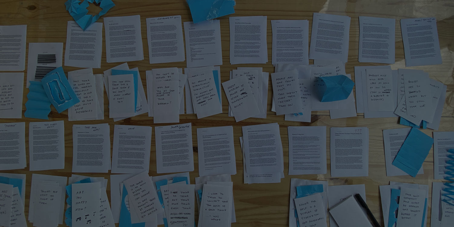 A photo of Adam's desk covered in printouts of text too small to read with handwritten notes and blue folded paper artwork strewn about.