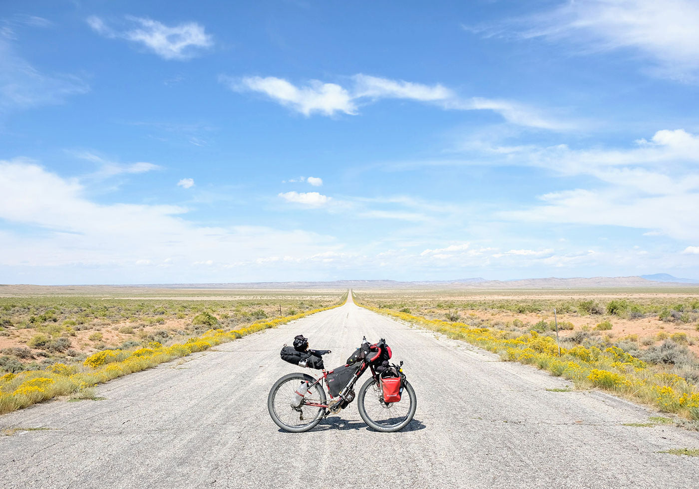 A beautiful view of a dirt road, stretching out into the distance with a bike in the foreground