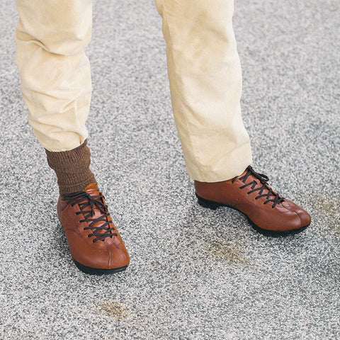 A rider wearing a pair of Quoc Tourer leather cycling shoes