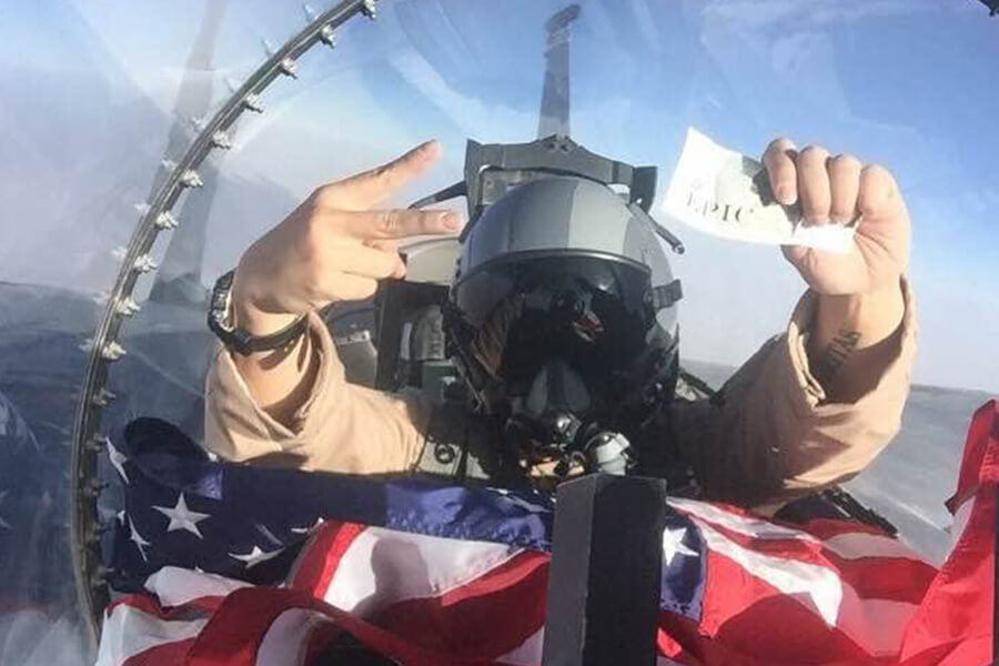 Pilot holding EPIC bar and American flag in cockpit