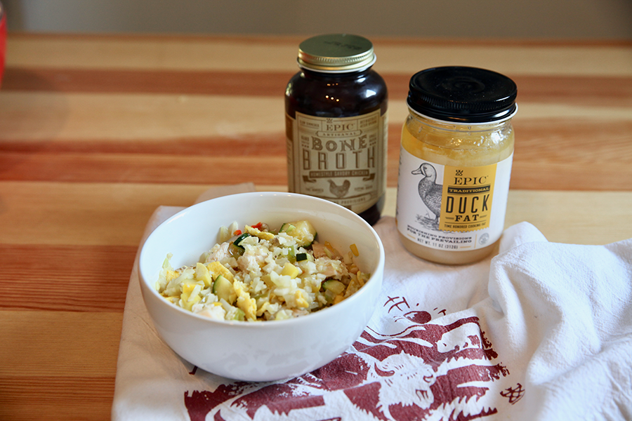 A bowl of cauliflower rice stir fry set next to a jar of EPIC duck fat and EPIC Homestyle Chicken broth.