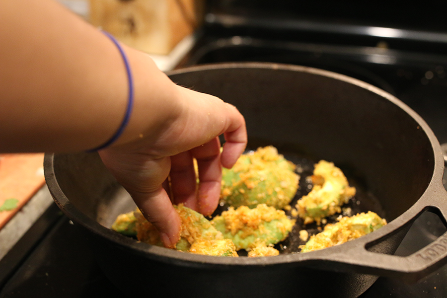 Breaded avocado cooking in a skillet.
