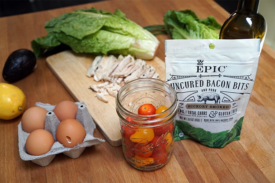 Items to make a Summer Cobb Salad. Head of romaine lettuce, cherry tomatoes, olive oil, lemon, avocado, four eggs, grilled chicken and a bag of EPIC Hickory Smoked Bacon Bits.