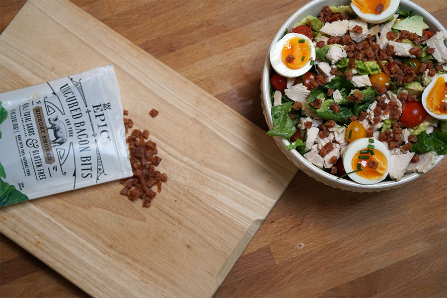 Image of a Summer Cobb Salad next to a cutting board with a bag of EPIC Hickory Smoked Bacon Bit's laying on top of it.
