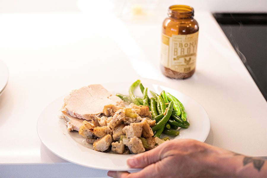 A plat of turkey, green beans, and EPIC's Bone Broth dressing being grabbed from the counter next to a bottle of EPIC Turkey Bone Broth.
