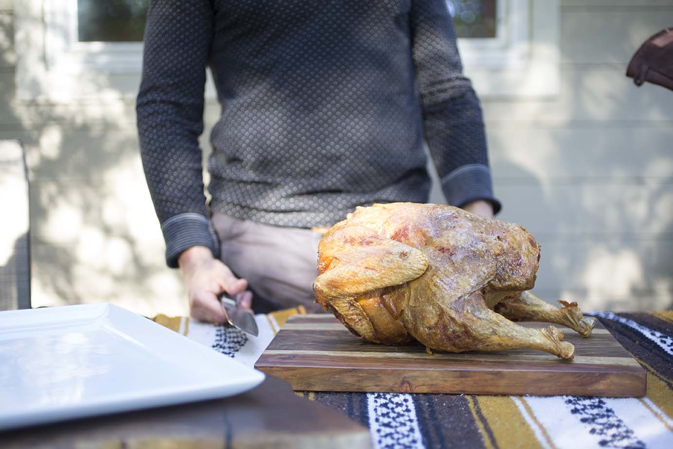 A crispy deep-fried turkey is shown on a wooden table in front of a man with knife