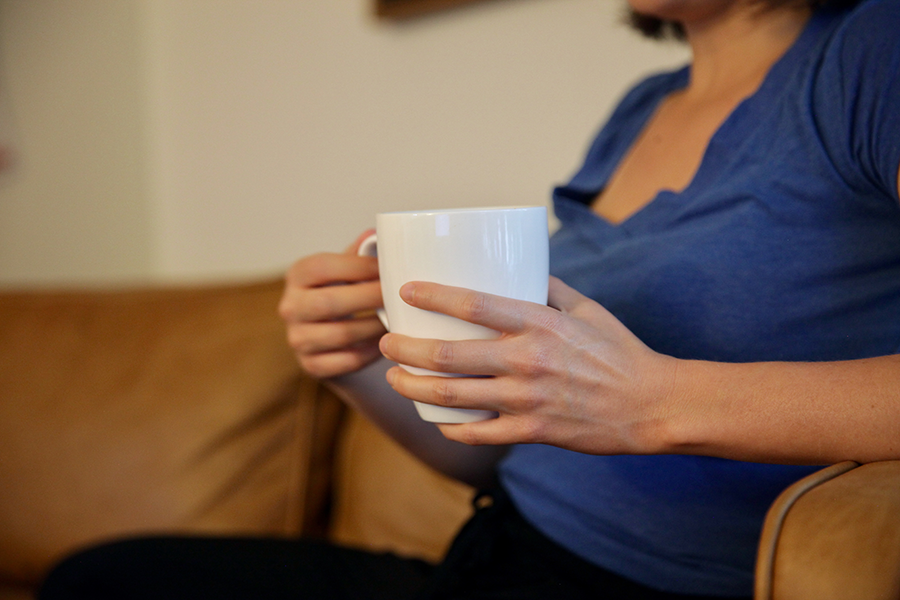Woman sitting on couch holding a cup of coffee.