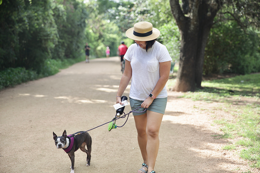 Woman walking with her dog on a trail.