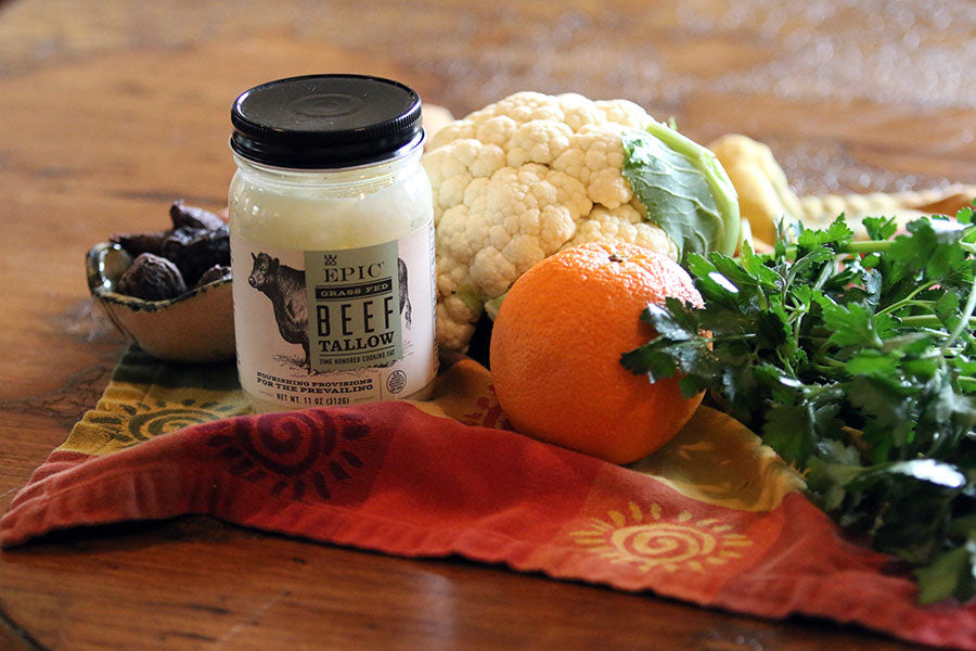 Head of cauliflower, jar of Epic Provision's Beef Tallow, a handful of arugula, a jar of apricots and an orange arranged on a kitchen towl.