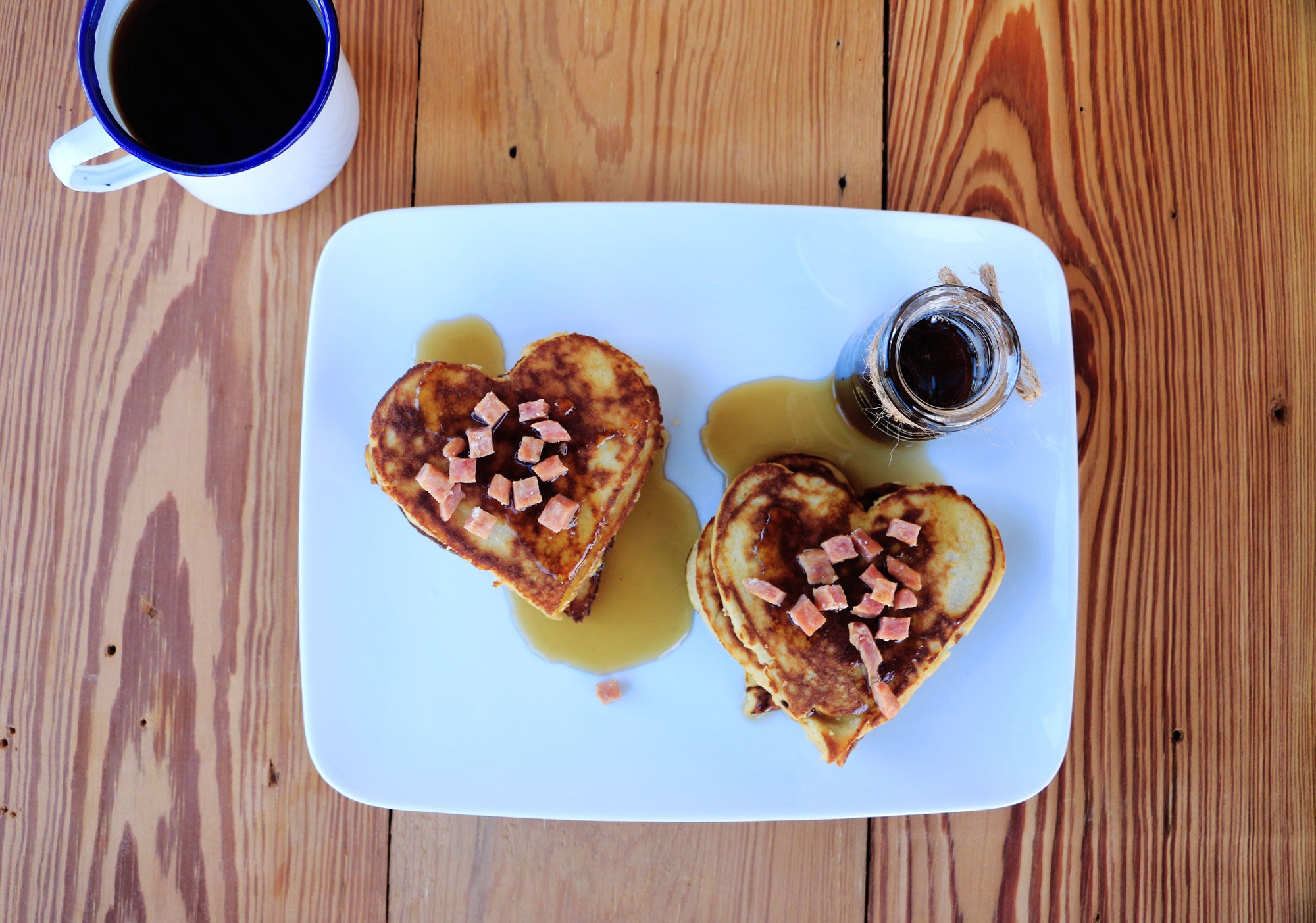Two stacks of heart-shaped pancakes on a white plate