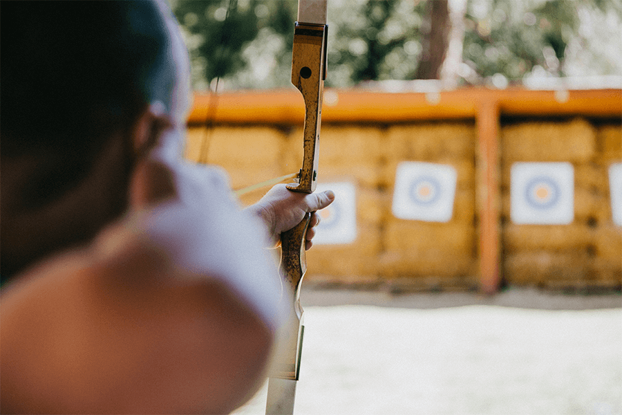 Man shooting arrow at outdoor targets