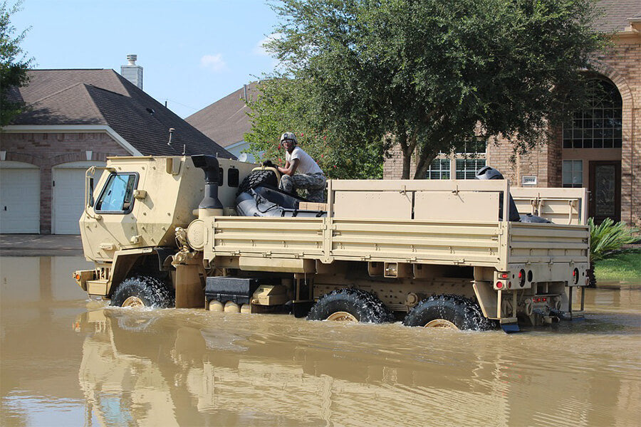 Military man sitting in tank in a flooded street