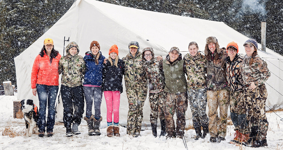 A group of women hunters stand in front of a white tent along with a few of their hunting dogs. Everyone's smiling and wearing hunting gear.
