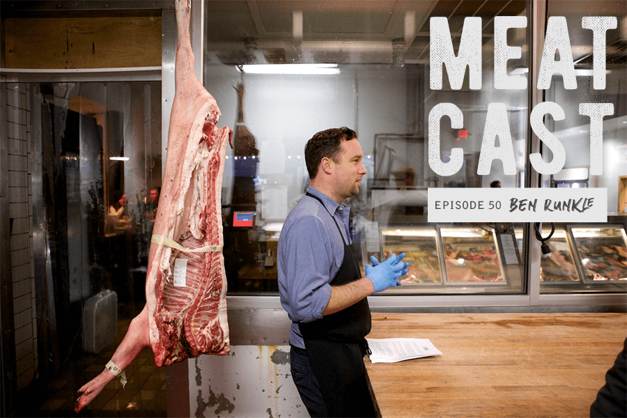 Butcher standing next to hanging carcass in kitchen