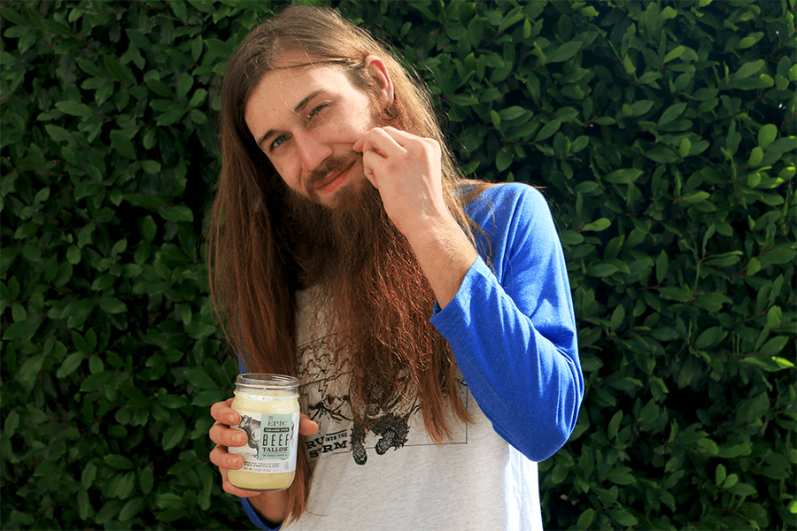 Man with long hair and facial hair putting animal oil on his mustache