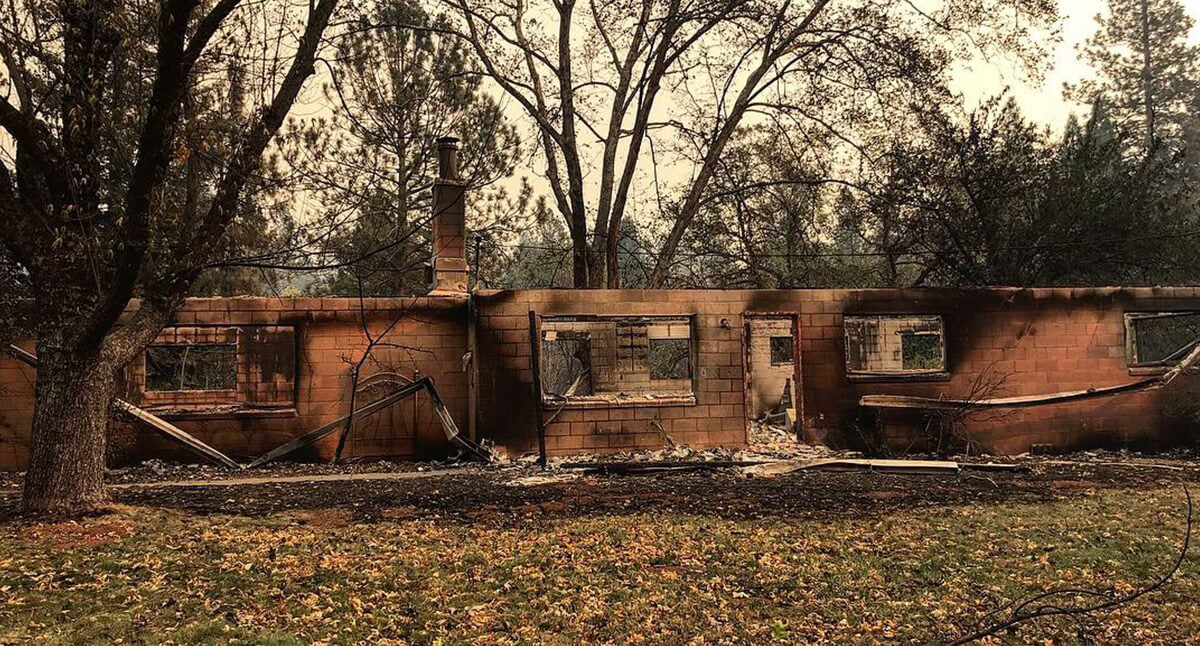 Image of the remains of a home in Paradise after the fire. Windows are broken and walls of the exterior have burnt areas..