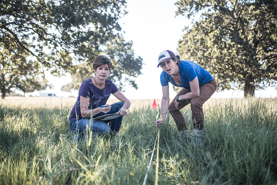 Two women taking soil measurements in grassy field