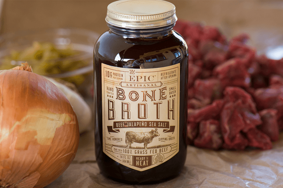 Jar of EPIC beef bone broth with onion and raw stew beef
