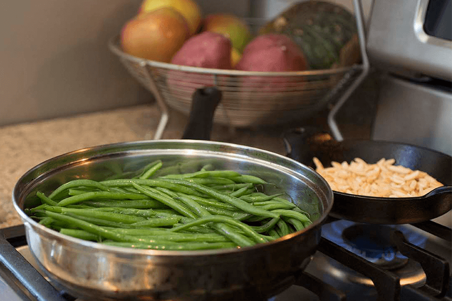 Green beans cooking on stove with bowl of fresh produce in background