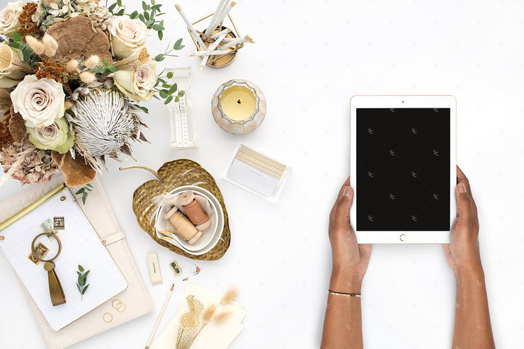 warm neutral desktop with florals and an ipad held by dark skin hands