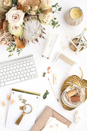 Styled stock photo with warm neutral colors, flowers, and a keyboard