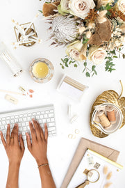 warm neutral desktop photo with neutral flowers, gold accents, and dark hands on a keyboard