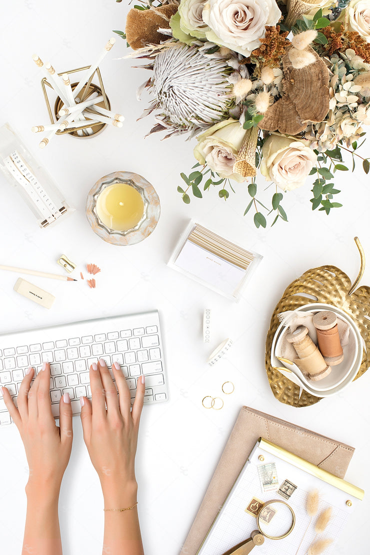 warm neutral desktop photo with neutral flowers, gold accents, and light hands on a keyboard
