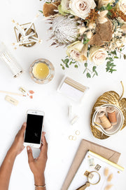 warm neutral desktop photo with neutral flowers, gold accents, and dark hands holding an iphone