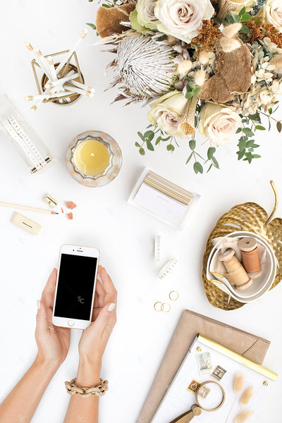 warm neutral desktop photo with neutral flowers, gold accents, and light hands holding an iphone